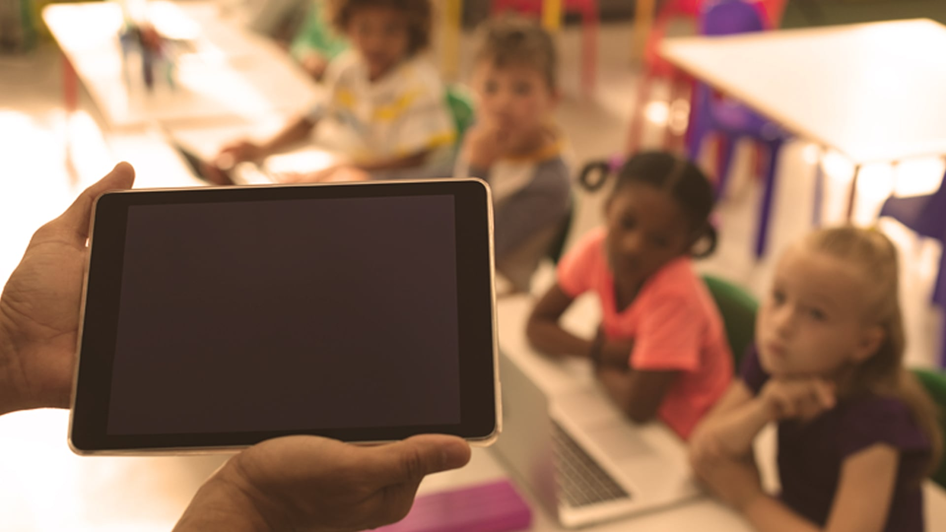 A teacher holds a tablet out to her young students