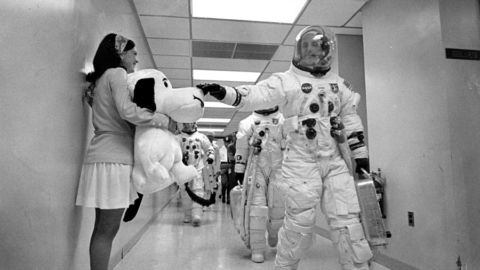 Astronauts walk through a corridor