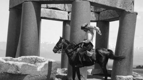 Black and white photo of a woman on a horse