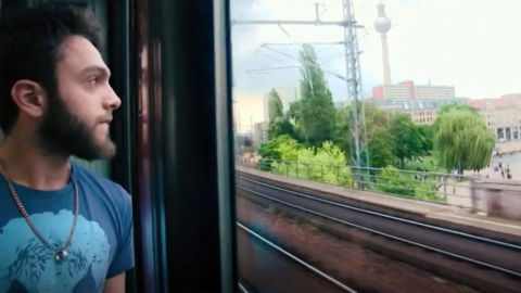 A man watches out the window of a train.