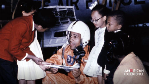 Ed Dwight, the first black astronaut trainee, shows an airplane model to children.