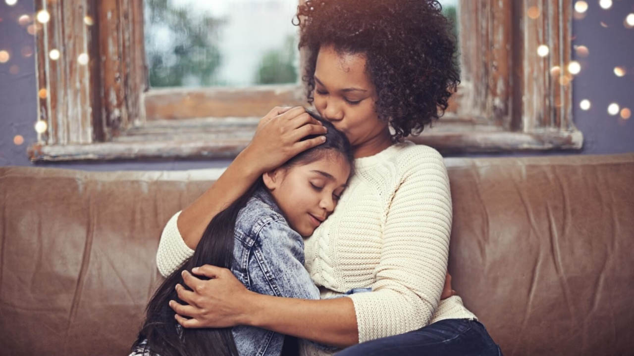 A woman hugs a young girl