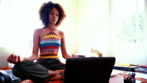 A woman meditates on a rug at home, next to a laptop, phone and office supplies.
