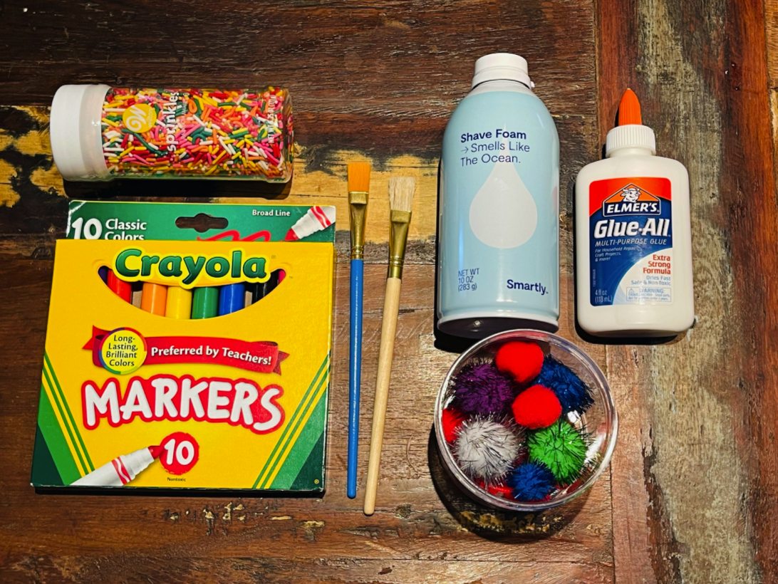 Photo features a box of 10 Crayola markers, bottle of sprinkles, a blue and tan paintbrush, a bottle of shaving cream, a package of colorful pom-poms (red, purple, blue, green and grey) and a bottle of Elmer's glue. The items are placed on a wood distressed table.