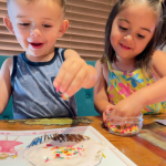 young boy and young girl smiling adding colorful sprinkles to a coloring book page