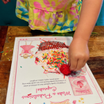 An up-close photo of a finished PINKALICIOUS cupcake that a young girl created. The cupcake is decorated with pink puffy paint, sprinkles and a red pom-pom as a cherry
