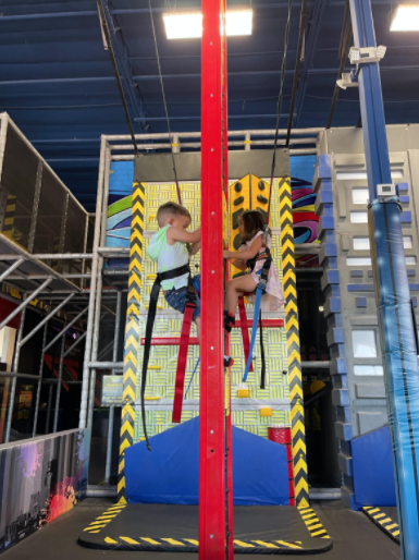 Two kids playing on climbing wall at indoor playground