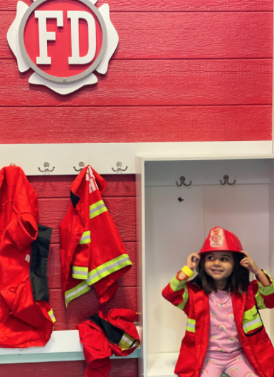 Girl wearing a fireman jacket and hat sitting in front of red-painted wall meant to replicate a fire station