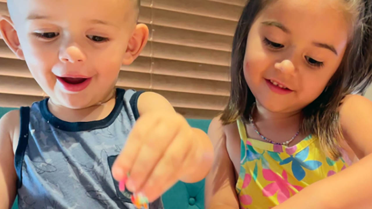 Two children add sprinkles to a craft project