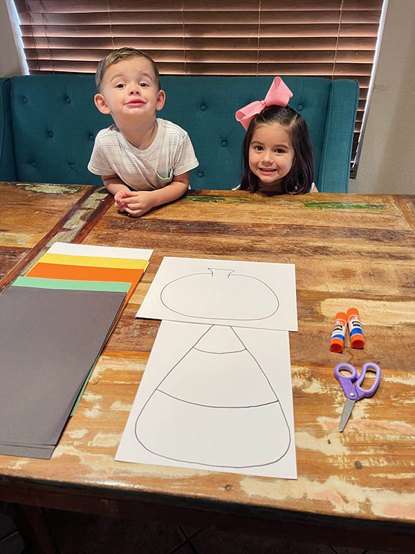 Materials for the project include colored paper, glue sticks and scissors. Logan and Olivia are seated at the table, ready to start!